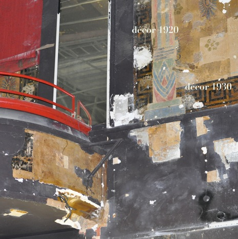 Photo de la grande salle avec différents sondages de dégagements des décors. On note la succession des couches qui recouvrent le décor de 1920: moquette rouge à droite, miroir, peinture noire et un nouveau décor datant de 1930.